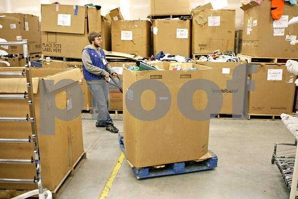 Rob Winner – rwinner@shawmedia.com<br /> <br /> Jake Michael moves a bin of donated items at Goodwill in DeKalb, Ill., Saturday, Nov. 24, 2012.