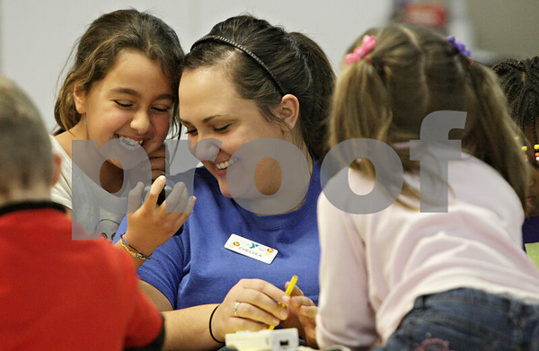 Rob Winner – rwinner@shawmedia.com<br /> <br /> Hanae Bahaji (left), 8, shows a video on her phone to Chelsea Most, a staff member at the YMCA, in the Activity Center at the Kishwaukee Family YMCA in Sycamore, Ill., Tuesday, Nov. 27, 2012.