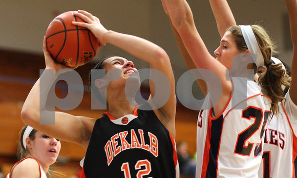 Kyle Bursaw – kbursaw@shawmedia.com<br /> <br /> DeKalb foreward Alexis Hammond looks for a shot under the basket with Naperville North's Kayla Sharples defending in the first quarter of DeKalb's 49-30 victory over Naperville North in the Lady War Hawk Thanksgiving girls basketball tournament at West Aurora High School on Friday, Nov. 23, 2012