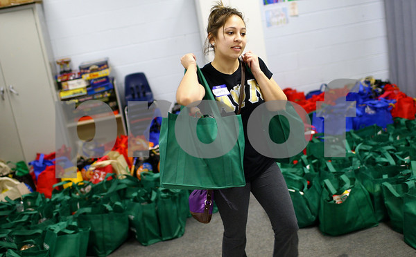 Kyle Bursaw – kbursaw@shawmedia.com<br /> <br /> Samantha Garbacz, an NIU student and Alpha Psi Lambda member, grabs a pair of bags meant for families of four or larger to bring to a family at the Salvation Army in DeKalb, Ill. on Tuesday, Nov. 20, 2012. Garbacz and other volunteers helped distribute food to more than 700 families.