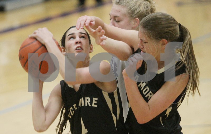 Rob Winner – rwinner@shawmedia.com<br /> <br /> Sycamore's Jenee Carlson (left) tries to shoot as Rochelle's Lauren Murphy (center) gets a hand in her face during the third quarter in Rochelle, Ill., Friday, Nov. 30, 2012. Rochelle defeated Sycamore, 52-49.
