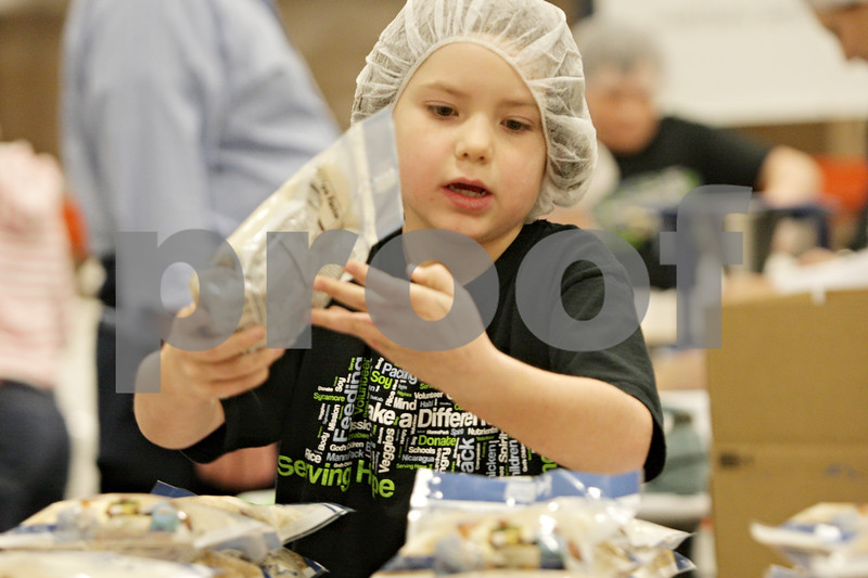 Rob Winner – rwinner@shawmedia.com<br /> <br /> Volunteer Megan Johnson, 7, of Maple Park, sorts rice packets during the first shift of the Feed My Starving Children MobilePack event at The Suter Co. Inc. in Sycamore, Ill., Friday, Nov. 16, 2012.