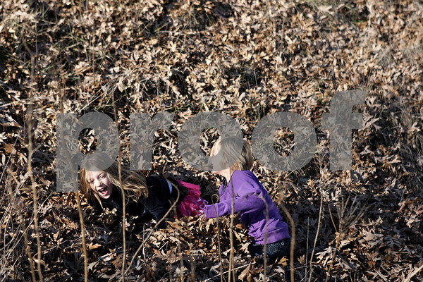 Rob Winner – rwinner@shawmedia.com<br /> <br /> Friends Ally Poegel (left), 6, and Madyson Huntington, 5, both of Kingston, play in the fallen leaves at the Prairie Oaks Forest Preserve in Kingston, Ill., Saturday, Nov. 17, 2012.
