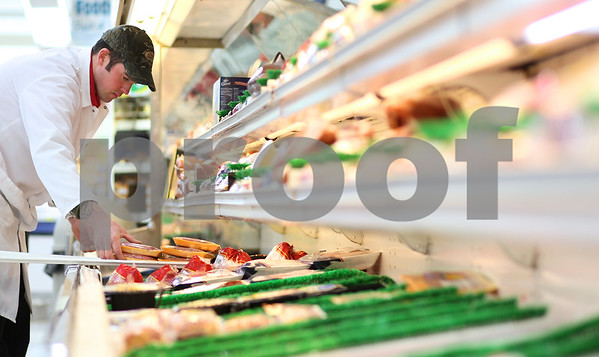 Kyle Bursaw – kbursaw@shawmedia.com<br /> <br /> Ryan Newman, meat manager at Brown's Country Market puts product in one of their cases in Sycamore, Ill. on Monday, Nov. 26, 2012.