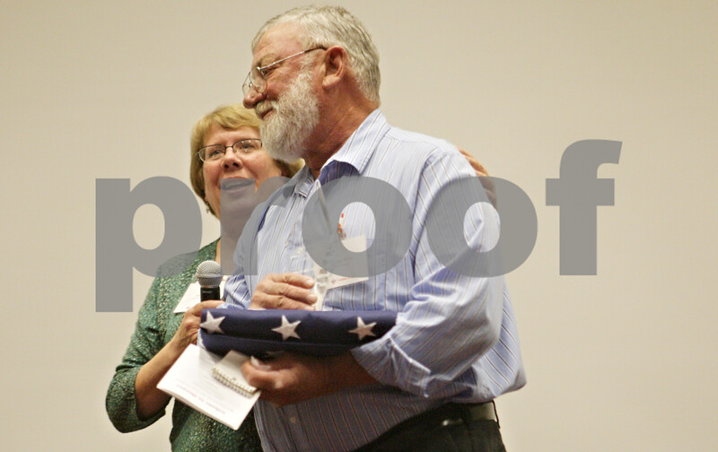 Rob Winner – rwinner@shawmedia.com<br /> <br /> Dennis Rehn (front) is helped off stage by Amy Polzin after being honored during the Three Fires Council Boy Scouts America 10th annual DeKalb County Tribute to Heroes at Kishwaukee College in Malta Thursday evening.