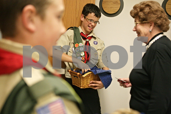 Rob Winner – rwinner@shawmedia.com<br /> <br /> Hank Barnes (center), 12, hands out badges to attendees of the Three Fires Council Boy Scouts America 10th annual DeKalb County Tribute to Heroes  at Kishwaukee College in Malta Thursday evening.Thursday, Oct. 4, 2012