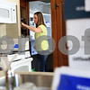 Kyle Bursaw – kbursaw@shawmedia.com<br /> <br /> Kara Burke, wife of DeKalb police officer Jared Burke, unpacks some of their belongings in the kitchen of their new home on North Eleventh Street on Friday, Sept. 28, 2012. Jared Burke will be living in the home as part of the resident officer program.
