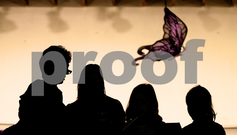 """Kyle Bursaw – kbursaw@shawmedia.com<br /> <br /> Several children, with help from a couple adults read 'Children Learn What They Live' by Dorothy Law Nolte on stage at Safe Passage's annual domestic violence vigil at the DeKalb Area Women's Center on Monday, Oct. 1, 2012. A butterfly ornament hangs overhead representing the theme of the vigil this year which was """"My New Wings: Renewed Sense of Hope."""""""