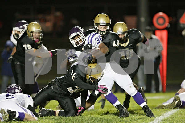Rob Winner – rwinner@shawmedia.com<br /> <br /> Rochelle running back Marquez Felix (36) is stood up by Sycamore's Jack Dargis (34) and Logan Schneider (44) on a fourth down during the second quarter in Sycamore Friday, Oct. 5, 2012. Sycamore took over on downs.