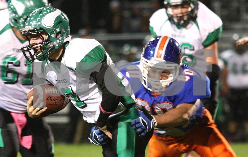 Kyle Bursaw – kbursaw@shawmedia.com<br /> <br /> North Boone quarterback Austin Baden escapes Genoa-Kingston's Sal Lopez (80) in the second quarter of the game against North Boone at Genoa-Kingston High School on Friday, Oct. 5, 2012.