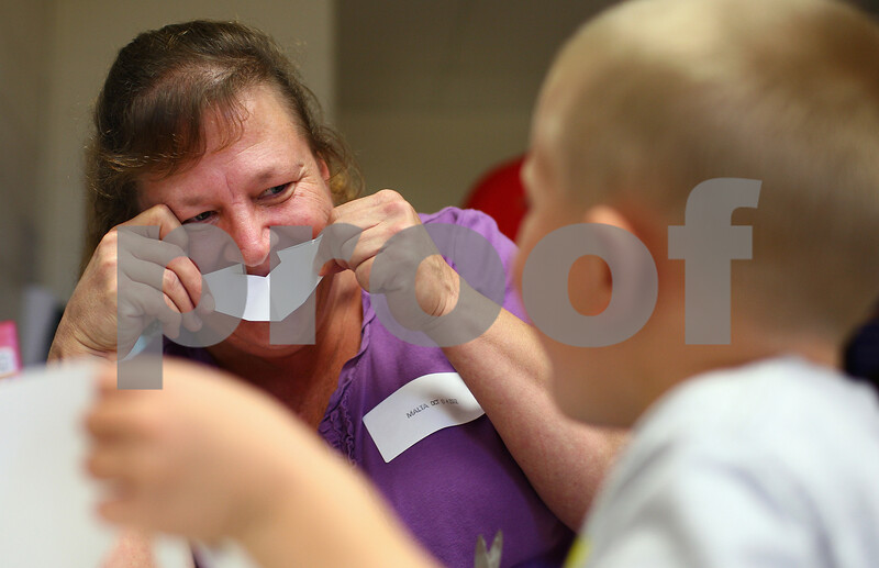 Kyle Bursaw – kbursaw@shawmedia.com<br /> <br /> Jeanette Edwards shows her grandson Connor McPartlin, 5, that a piece of scrap paper he cut while working on a project resembles a mustache during grandparent day at Malta Elementary on Thursday, Oct. 4, 2012.