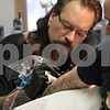 "Rob Winner – rwinner@shawmedia.com<br /> <br /> Rick ""Spider"" Kramer, owner of Spider Tattooz in Sycamore, works on a tattoo for fellow artist Ryan Fleetwood on Thursday afternoon. On Sunday, Kramer and three other artists raised funds to help his family friend Caleb Medley, who is in a coma after being shot during the Aurora, Colo., shootings. A larger fundraiser is set for this weekend at Moose Lodge with a dinner and auction."