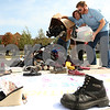Kyle Bursaw – kbursaw@shawmedia.com<br /> <br /> Lisa Oller and John Mulvey (right), both Famous Footwear employees and NIU students, dump donated shoes onto their pile outside the Holmes Student Center for the annual Day Without Shoes put on by NIU's Engineers Without Borders club on Thursday, Oct. 4, 2012.