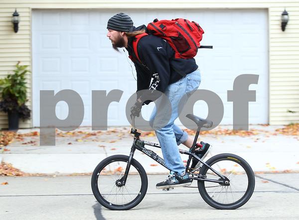 Kyle Bursaw – kbursaw@shawmedia.com<br /> <br /> Eric Carlson bikes down Charles Street in Sycamore while running a few errands before work on Tuesday, Oct. 9, 2012.