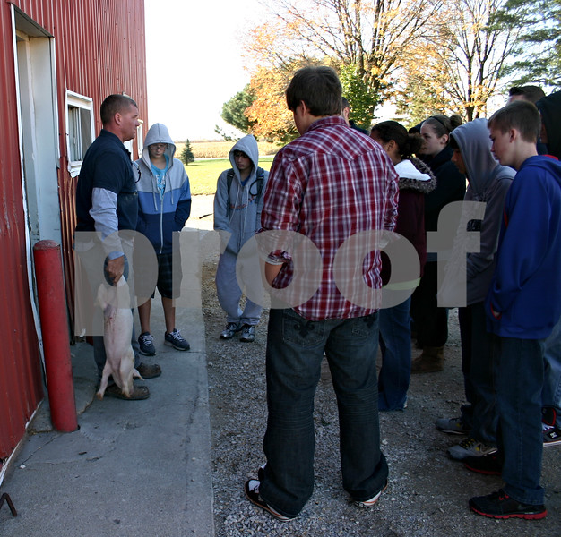 Jeff Engelhardt – jengelhardt@shawmedia.com<br /> Steve Ward, of Old Elm Farms, shows a group of eighth-grade  Sycamore Middle School students how to properly pick up a pig Thursday at his farm.