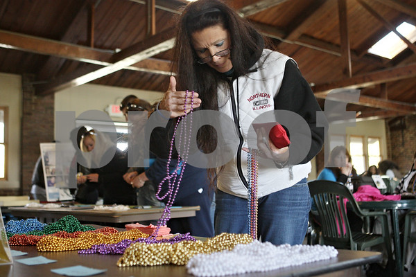 Rob Winner – rwinner@shawmedia.com<br /> <br /> Ruthann Slayton, a minister for the DeKalb and Sycamore communities, chooses from a selection of honor beads before the start of the DeKalb Out of the Darkness Community Walk event at Hopkins Park Saturday morning.