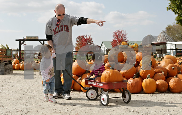 Rob Winner – rwinner@shawmedia.com<br /> <br /> After picking their pumpkins, Justin Wagner, of Naperville, directs his twin daughters, Madison (left), 3, and Sabrina, 3, toward the exit at Kuipers Family Farm in Maple Park Friday, Sept. 28, 2012.