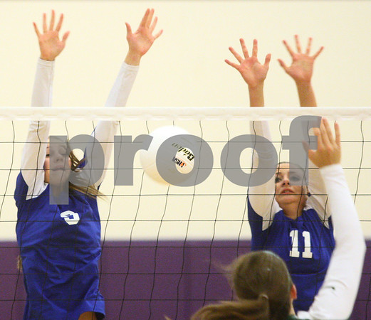 Kyle Bursaw – kbursaw@shawmedia.com<br /> <br /> Genoa-Kingston's Samantha Hansel (left) gets a block against St. Edward as teammate Tori Hensley (right) also attempts to block in the Class 3A Hampshire regional quarterfinal at Hampshire High School on Monday, Oct. 22, 2012. St. Edward defeated Genoa-Kingston 25-20, 25-16.