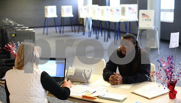 Kyle Bursaw – kbursaw@shawmedia.com<br /> <br /> Deputy Registrar Nancy Higdon (left) registers NIU student Herby Weathers, 24, to vote in the Holmes Student Center on Monday, Oct. 22, 2012.