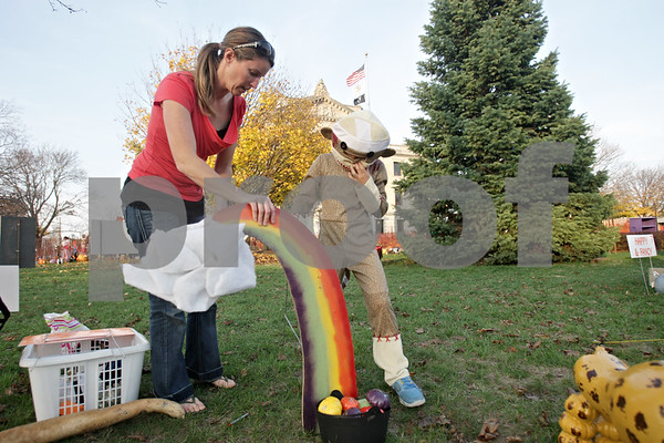 Rob Winner – rwinner@shawmedia.com<br /> <br /> Sycamore residents Maggie Peck (left) and her daughter Jaden Peck, 9, construct Jaden's pumpkin entry on the lawn outside the DeKalb County Courthouse in Sycamore at the Sycamore Pumpkin Festival Wednesday evening.<br /> <br /> Wednesday, Oct. 24, 2012