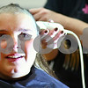 Kyle Bursaw – kbursaw@shawmedia.com<br /> <br /> Seventh-grader Grace Ballas' eyes well up as her cousin Kari Hutchinson, a hair stylist at Perfect Reflections in DeKalb, shaves Ballas' head during an all-school assembly at Somonauk Middle School on Wednesday, Oct. 31, 2012. Ballas raised $2,758 for the Susan G. Komen Foundation.