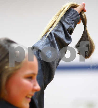 Kyle Bursaw – kbursaw@shawmedia.com<br /> <br /> Seventh-grader Grace Ballas holds up the first chunk of her hair shaved off during an all-school assembly at Somonauk Middle School on Wednesday, Oct. 31, 2012. Ballas raised $2,758 for the Susan G. Komen Foundation.