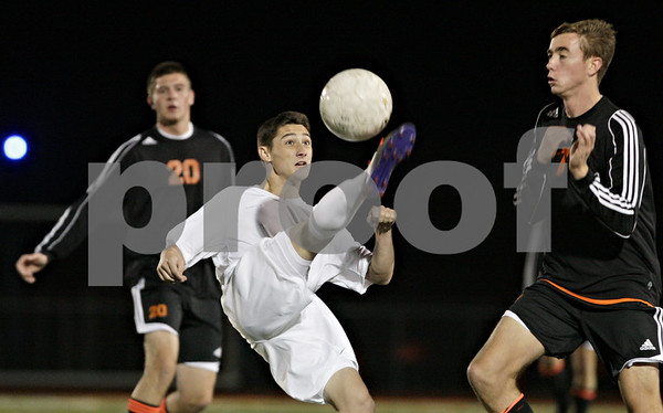 Rob Winner – rwinner@shawmedia.com<br /> <br /> Jacobs' Austin Ryan (center) controls a ball in the first half of the Class 3A DeKalb Regional semifinal on Tuesday, Oct. 16, 2012. DeKalb defeated Jacobs, 1-0.