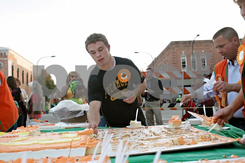 Rob Winner – rwinner@shawmedia.com<br /> <br /> The 2012 Sycamore Pumpkin Festival Grand Marshal Austin Culton cuts cake for guests at the festival in downtown Sycamore Wednesday evening.<br /> <br /> Wednesday, Oct. 24, 2012