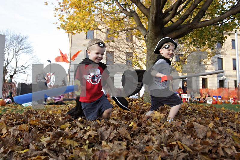 Rob Winner – rwinner@shawmedia.com<br /> <br /> Nicholas Hlubek (left), 3, of Sycamore, and his brother Owen Hlubek, 5, run through a pile of leaves outside the DeKalb County Courthouse in Sycamore at the Sycamore Pumpkin Festival Wednesday evening.<br /> <br /> Wednesday, Oct. 24, 2012