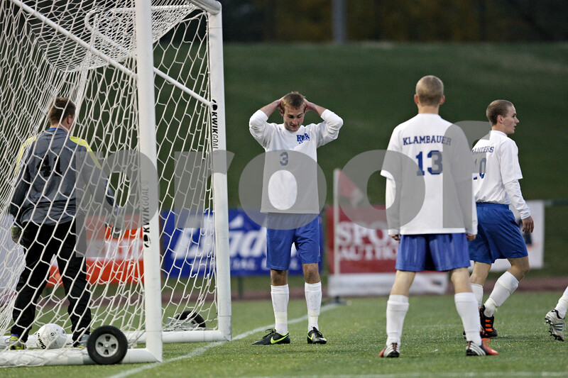 Rob Winner – rwinner@shawmedia.com<br /> <br /> Hinckley-Big Rock's Christian Johnsen (3) reacts after an Alton Marquette goal as goalkeeper Jason Bohannon (left) retrieves the ball in the second half during the Class 1A State semifinal in Normal, Ill., Friday, Oct. 26, 2012. Alton Marquette defeated H-BR, 4-3.