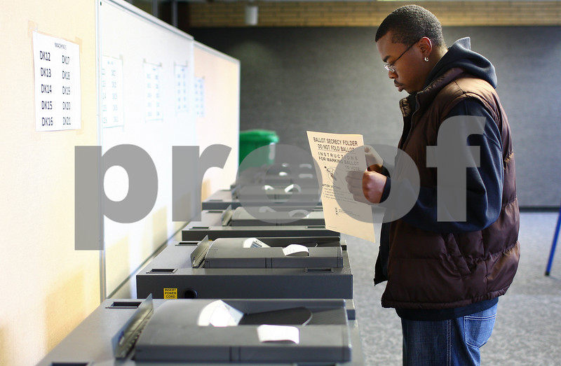 Kyle Bursaw – kbursaw@shawmedia.com<br /> <br /> Northern Illinois University student Herby Weathers, 24, puts his completed ballot into one of the counting machines in the Holmes Student Center on Monday, Oct. 22, 2012.