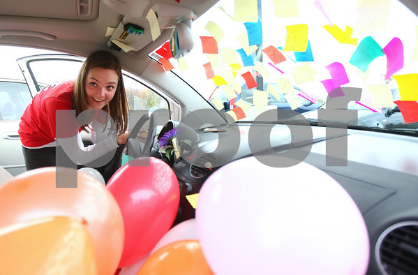 Kyle Bursaw – kbursaw@shawmedia.com<br /> <br /> DeKalb High School senior Jaylene Thompson clears sticky notes off of the windshield of her white Volkswagen Beetle as she talks to her Poms advisor Julie Craven (not pictured), who filled the car with balloons and covered it with sticky notes in the high school's parking lot with the help of some of the other girls on the Poms squad on Tuesday, Oct. 23, 2012.  The car was the latest in an ongoing prank war between the two that started a few weeks earlier over Thompson's desire for the Poms to perform a Taylor Swift song.