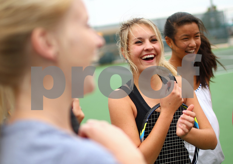Kyle Bursaw – kbursaw@shawmedia.com<br /> <br /> Sycamore tennis players Alexa Farris (center) and Angelina Ye (right) laugh while discussing details about their upcoming matches at the end of practice on Tuesday, Oct. 9, 2012.