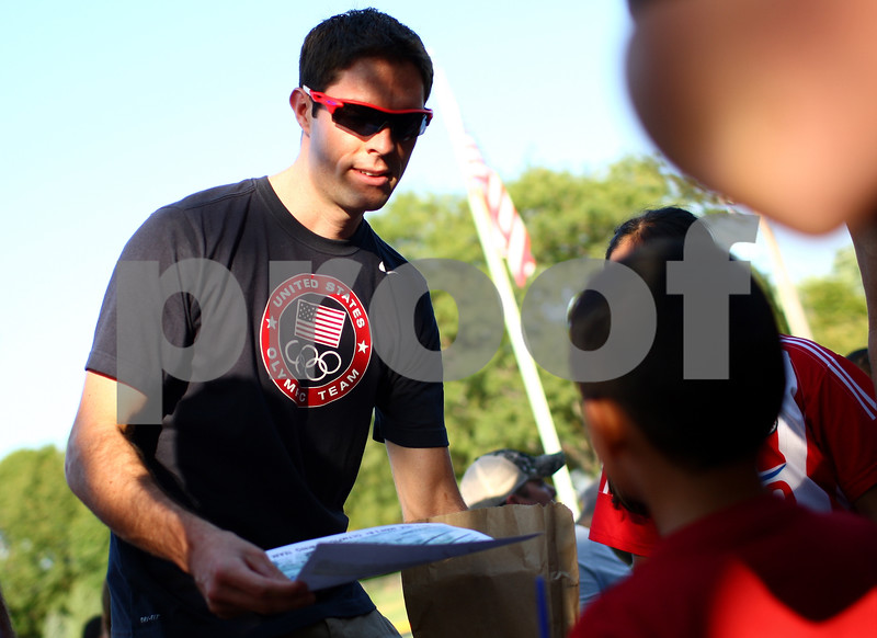 Kyle Bursaw – kbursaw@shawmedia.com<br /> <br /> Ross James, a DeKalb native who along with his twin brother James was on the U.S. men's Olympic rowing team, hands out an autographed photo of the team to students at Jefferson Elementary on Thursday, Sept. 6, 2012.