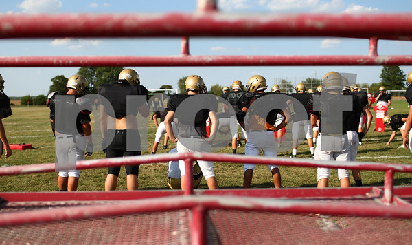 Kyle Bursaw – kbursaw@shawmedia.com<br /> <br /> Seen through some of the practice equipment, a squad of Sycamore's offensive players watch from the sidelines as another offensive squad takes on the scout defense at practice on Tuesday, Sept. 4, 2012.