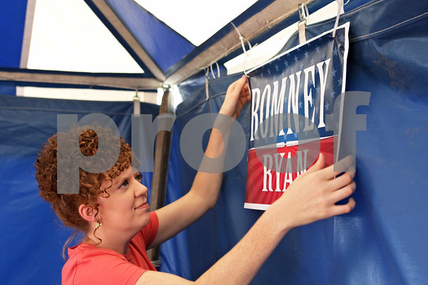 Rob Winner – rwinner@shawmedia.com<br /> <br /> Shaina Busch, of Sandwich, hangs a sign to show support for Mitt Romney and Paul Ryan inside the DeKalb County Republicans' tent at the Sandwich Fairgrounds on Tuesday afternoon.
