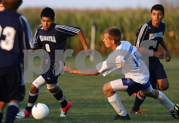 Kyle Bursaw – kbursaw@shawmedia.com<br /> <br /> Hiawatha's Reyman Solis (8) controls the ball as Hinckley-Big Rock's Billy Weissinger (14) pursues during the first half of the game in Hinckley, Ill. on Wednesday, Sept. 12, 2012.