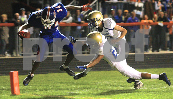 Kyle Bursaw – kbursaw@shawmedia.com<br /> <br /> A pair of Rockford Christian defenders force Genoa-Kingston's Gabe Williams out of bounds just shy of the goal line in the second quarter of the game in Genoa, Ill. on Friday, Sept. 14, 2012.