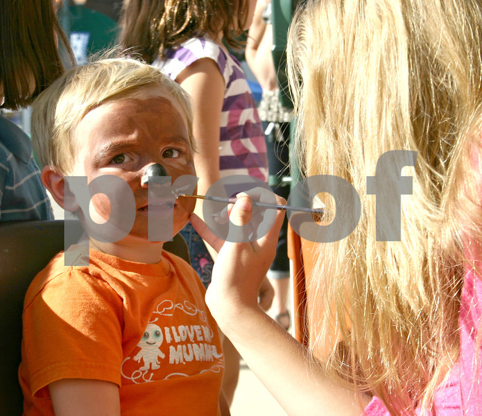 Patrick Latham, 2, of DeKalb, gets his face painted to look like a puppy by Elena Edwards, a volunteer from Art Attack, Saturday at the 12th annual Sycamore Block Party.<br /> <br /> By Nicole Weskerna - nweskerna@shawmedia.com