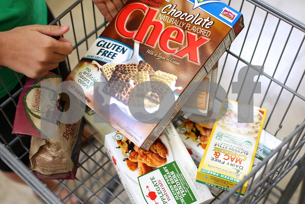Kyle Bursaw – kbursaw@shawmedia.com<br /> <br /> Katie Myers, 25, puts gluten-free chocolate Chex into her cart while shopping at Sycamore Hy-Vee on Thursday, Sept. 20, 2012. Myers has been eating gluten-free for about six years.