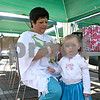 Juana Parra of Sycamore braids the hair of her granddaughter, Ella Parra, 1, who is dress in a traditional Mexican folk dancing outfit at the ninth annual Conexion Comunidad Fiesta in downtown DeKalb Saturday.<br /> <br /> By Nicole Weskerna - nweskerna@shawmedia.com