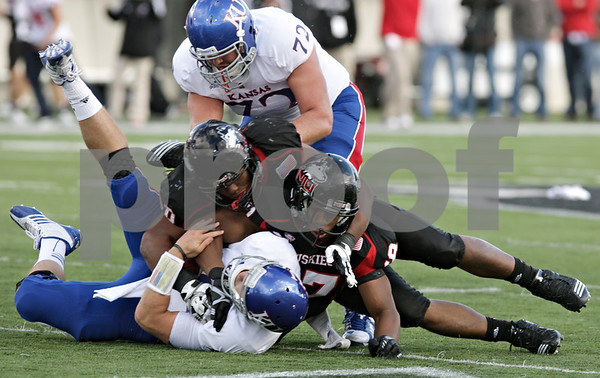 Rob Winner – rwinner@shawmedia.com<br /> <br /> Kansas quarterback Dayne Crist (bottom) is sacked for a 6-yard loss by Northern Illinois defensive end Joe Windsor (right) as defensive end Alan Baxter assists on the play during the fourth quarter at Huskie Stadium in DeKalb, Ill., on Saturday, Sept. 22, 2012. Northern Illinois defeated Kansas, 30-23.