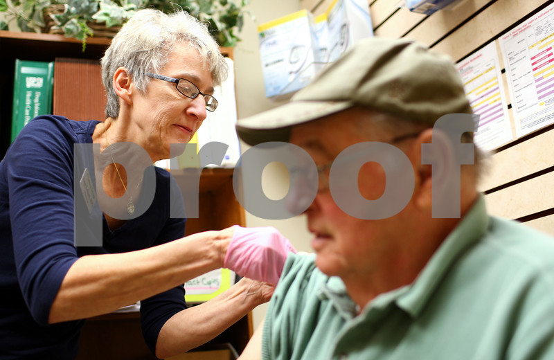 Kyle Bursaw – kbursaw@shawmedia.com<br /> <br /> Ann Lehan, owner and pharmacist at Lehan Drugs, gives a flu vaccination to Sycamore resident Donald Schiltz on Thursday, Sept. 20, 2012.