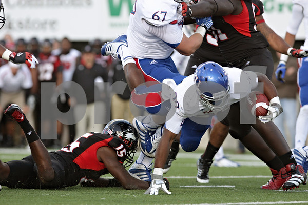 Rob Winner – rwinner@shawmedia.com<br /> <br /> Kansas halfback James Sims (29) is tripped up by Northern Illinois defensive back Jimmie Ward (15) after a 1-yard gain during the third quarter at Huskie Stadium in DeKalb, Ill., on Saturday, Sept. 22, 2012. Northern Illinois defeated Kansas, 30-23.