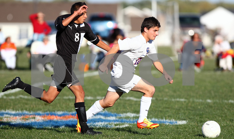 Kyle Bursaw – kbursaw@shawmedia.com<br /> <br /> Genoa-Kingston's Devon Tijerina (10) chases after the ball with Harvard's Jerry Martinez (8) pursuing in the first half of the game. Harvard defeated Genoa-Kingston 1-0 in Genoa, Ill. on Monday, Sept. 24, 2012.