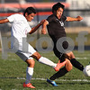 Kyle Bursaw – kbursaw@shawmedia.com<br /> <br /> Genoa-Kingston's Cristian Camargo passes past Harvard's Gabriel Juarez in the first half of the game. Harvard defeated Genoa-Kingston 1-0 in Genoa, Ill. on Monday, Sept. 24, 2012.