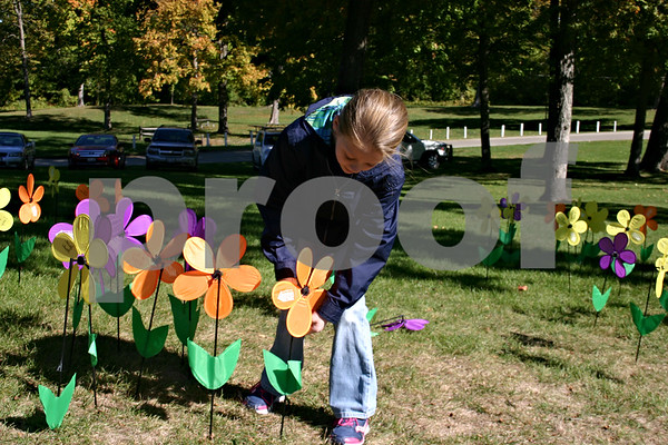 "Jenna Strohschein of South Elgin ""plants"" a flower in the memorial garden set up Sunday in Hopkins Park as part of DeKalb's Walk to End Alzheimer's, organized by the Alzheimer's Association. Walk participants raised more than $30,000.<br /> <br /> Caitlin Mullen - cmullen@shawmedia.com"