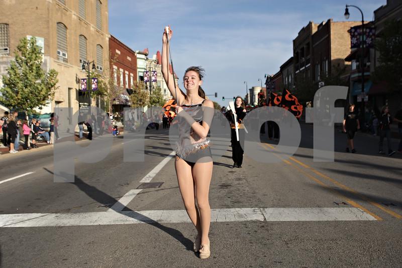 Rob Winner – rwinner@shawmedia.com<br /> <br /> Senior Allison Hunter-Rosene twirls her baton while leading the DeKalb High School homecoming parade west on East Lincoln Highway in downtown DeKalb on Thursday evening.