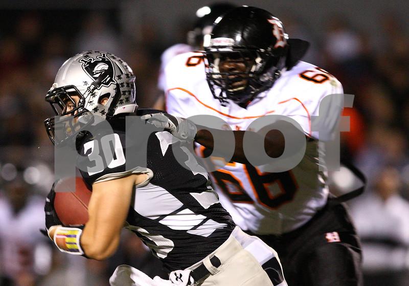 Kyle Bursaw – kbursaw@shawmedia.com<br /> <br /> Kaneland running back Jesse Balluff gets by DeKalb's Jonathon Bell in the first quarter of the game at Kaneland High School on Friday, Sept. 28, 2012.
