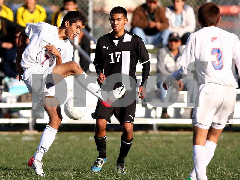 Kyle Bursaw – kbursaw@shawmedia.com<br /> <br /> Genoa-Kingston's Francisco Marquez (7) kicks away from Harvard's Christian Carrillo (17) during the first half of the game. Harvard defeated Genoa-Kingston 1-0 in Genoa, Ill. on Monday, Sept. 24, 2012.